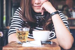 Uma mulher asiática que senta-se no café com os copos do café e do chá quentes Foto de Stock