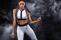 Uma mulher atlética forte no fundo preto que veste na motivação branca do sportswear, da aptidão e do esporte Conceito do esporte imagens de stock royalty free