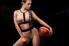 Uma mulher atlética forte no fundo preto que veste no sportswear amarelo da forma com bola, aptidão e esporte do basquetebol fotografia de stock royalty free