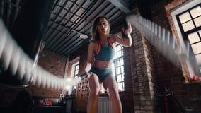 Uma mulher atlética que faz o crossfit no gym Treinando suas m?os com as cordas que batem no assoalho vídeos de arquivo