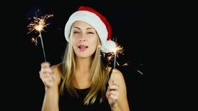 Uma mulher atrativa com as duas luzes de Bengal que dançam no fundo preto, conceito: celebração do Natal e do filme