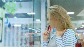 Uma mulher atrativa com vista dyal dos sacos de compras em uma janela da loja, e então vai resolutamente à loja vídeos de arquivo