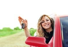 Uma mulher atrativa no carro vermelho guarda uma chave do carro em sua mão Fotografia de Stock