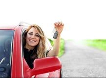 Uma mulher atrativa no carro vermelho guarda uma chave do carro em sua mão Fotografia de Stock Royalty Free