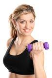 Uma mulher atrativa nova que exercita com pesos Foto de Stock
