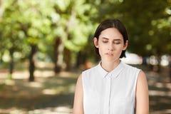Uma mulher atrativa profissional em uma camisa ocasional em um fundo natural A senhora segura é de passeio e de vista para baixo  fotografia de stock