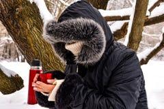 Uma mulher bebe o chá quente derramado de uma garrafa térmica imagem de stock royalty free