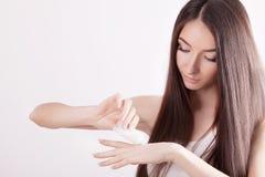 Uma mulher bonita Ásia usando um produto dos cuidados com a pele, creme hidratante ou imagens de stock