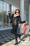 Uma mulher bonita anda através da cidade na compra, ela está muito feliz das compras nas vendas do período Conceito: forma, shopp Fotografia de Stock Royalty Free