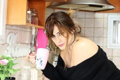 Uma mulher bonita bebe o café na cozinha Foto de Stock