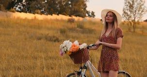 Uma mulher bonita com uma bicicleta em um chapéu e em um vestido leve do verão vem com as flores em uma cesta e em sorrisos filme