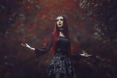 Uma mulher bonita com pele pálida e cabelo vermelho longo em um vestido preto e no crownk preto Bruxa da menina com vampiro imagem de stock royalty free