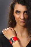 Uma mulher bonita com um bracelete vermelho Fotos de Stock