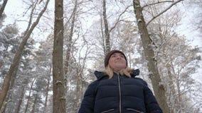 Uma mulher bonita da menina anda através da floresta, olha ao redor imagens de stock