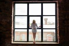 Uma mulher bonita em uma camisa está estando na soleira e olha para fora a janela Fotografia de Stock