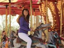 Uma mulher bonita em um carrossel Fotografia de Stock Royalty Free