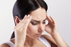 Uma mulher bonita em um fundo, em um esforço e em uma dor de cabeça cinzentos com dores de cabeça da enxaqueca, atracou-se com do Fotos de Stock Royalty Free