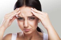 Uma mulher bonita em um fundo, em um esforço e em uma dor de cabeça cinzentos com dores de cabeça da enxaqueca, atracou-se com do Imagens de Stock Royalty Free