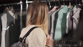 Uma mulher bonita escolhe a roupa para seu vestuário novo, ela olha como um estilista video estoque