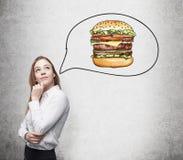 Uma mulher bonita está pensando sobre o hamburguer Um conceito do fast food imagens de stock royalty free