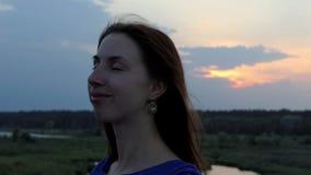 Uma mulher bonita gerencie sua cara e sorri em um banco do lago no slo-mo vídeos de arquivo