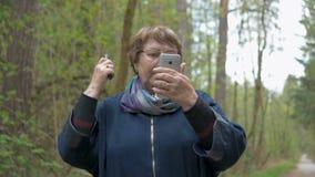 Uma mulher bonita idosa olha em um smartphone e traz a beleza, penteia seu cabelo, ajusta-a roupa Para uma caminhada dentro vídeos de arquivo