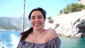 Uma mulher bonita morena está desfrutando de uma viagem de barco em câmera lenta em um dia ensolarado video estoque