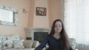 Uma mulher bonita nova anda através da porta à sala de jantar e senta-se na tabela a ela amado Uma menina agradável dentro filme
