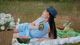 Uma mulher bonita nova em um chapéu e em um vestido está bebendo a limonada de uma lata ao sentar-se em uma manta na grama verde vídeos de arquivo