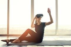 Uma mulher bonita nova em vidros da realidade virtual faz a ginástica aeróbica remotamente Conceito futuro da tecnologia Imagem l Fotografia de Stock