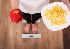 Uma mulher bonita nova está nas escalas e faz uma escolha entre uma maçã e microplaquetas de batata O conceito de comer saudável  Imagem de Stock Royalty Free