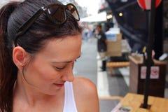 Uma mulher bonita nova que refresca-se com uma cerveja em um de muitos barras e restaurantes pequenos perto do mercado de peixes  Imagens de Stock