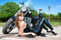 Uma mulher bonita próximo pela motocicleta foto de stock