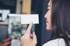 Uma mulher bonita que guarda e que mostra o cartão vazio com cara do smiley Fotografia de Stock
