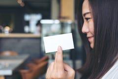 Uma mulher bonita que guarda e que mostra o cartão vazio com cara do smiley Imagens de Stock