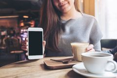 Uma mulher bonita que guarda e que mostra o telefone celular branco com a tela preta vazia do desktop com os copos de café na tab Imagem de Stock Royalty Free