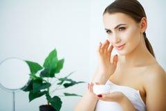 Uma mulher bonita que usa um produto, um creme hidratante ou uns lótus dos cuidados com a pele fotos de stock