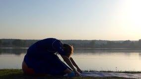 Uma mulher bonita senta-se em uma bola vermelha em um banco do lago vídeos de arquivo