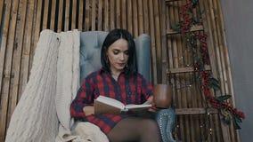 Uma mulher bonita senta-se em uma cadeira em uma noite do inverno, lê-se um livro interessante e bebe-se o chocolate quente vídeos de arquivo