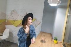 Uma mulher bonita senta-se em um café com um interior à moda e em uma xícara de café na tabela Fotos de Stock
