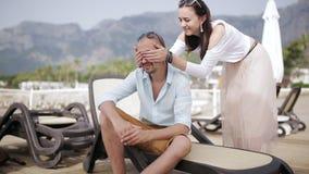 Uma mulher bonita vem ao assento em um indiv?duo do vadio do sol e abra?a-o vídeos de arquivo