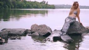 Uma mulher bonito com o cabelo louro longo vestido em um terno de sirene, levantando na câmera, sentando-se em uma pedra grande n video estoque