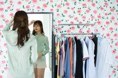 Uma mulher bonito está olhando o mirrow em sua sala fotografia de stock royalty free