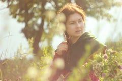 Uma mulher branca caucasiano nova feliz com cabelo vermelho longo é de sorriso e de riso com um ramalhete das flores em suas mãos imagem de stock