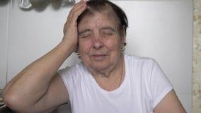 Uma mulher caucasiano idosa idosa está tendo uma dor de cabeça severa video estoque