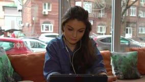 Uma mulher caucasiano irritada da menina que surfa em uma tabuleta no café e no café bebendo filme