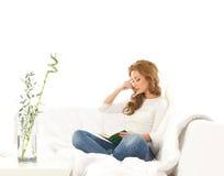 Uma mulher caucasiano nova que lê um livro em um sofá foto de stock