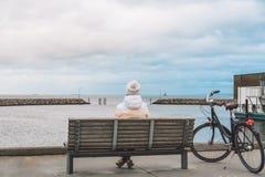 Uma mulher caucasiano nova senta-se com sua parte traseira em um banco de madeira que negligencia o mar Báltico na frente marítim fotografia de stock royalty free