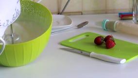 Uma mulher chicoteia o creme com um misturador Ao lado de outros ingredientes para fazer a sobremesa Açúcar e morangos filme