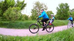 Uma mulher com as crianças que montam bicicletas no parque video estoque
